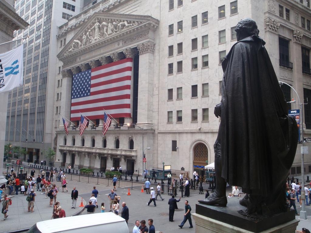 statue of george washington near building displaying american flag
